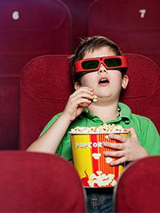 아이가 영화관에서 영화를 보며 팝콘을 먹고 있는 모습입니다.