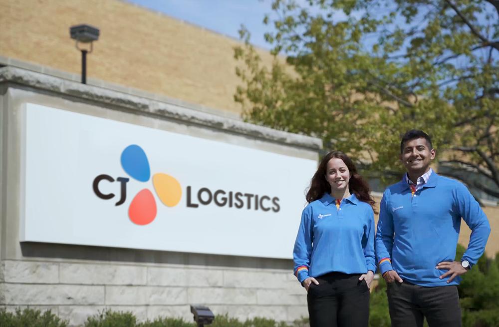 """在品牌整合为""""CJ Logistics""""的CJ物流美国综合子公司牌匾前,员工们正在拍照留念。"""
