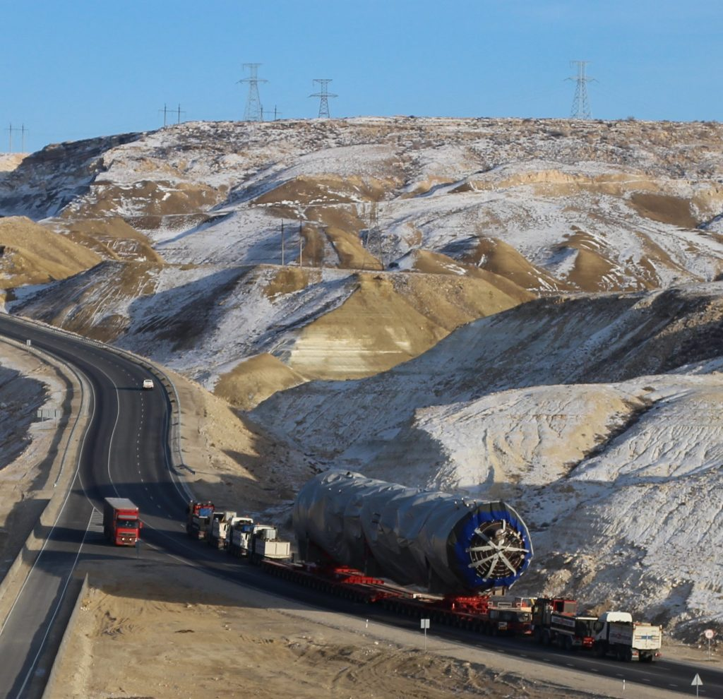 "Logistics of an ultra-heavy plant equipment project conducted by CJ Logistics in 2018. Heavy trucks heading to Uzbekistan are going up the Manata hill in Mangystau. To go up an 8-degree slope, ""power chain"" technology is applied, which connects a special towing vehicle with a strong output of at least 500 horsepower to the front and rear of the module trailer that carries the heavy cargo."