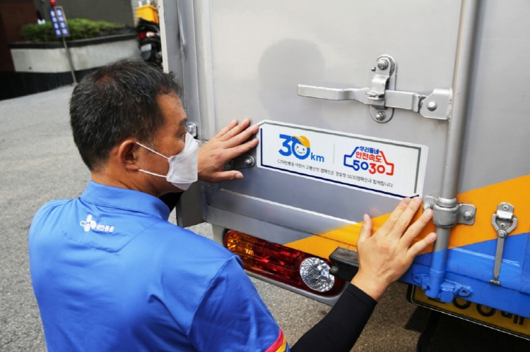 A CJ Logistics delivery driver putting on a traffic safety guard sticker that specifies safe speed standards on a delivery truck.