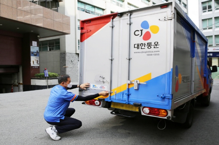 CJ Logistics delivery driver attaching a traffic safety guard sticker that specifies safe speed standards on a delivery truck.