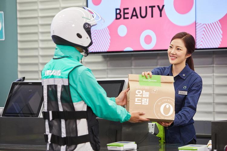 CJ올리브영 매장에서 여성 구성원이 '오늘드림' 상품을 배달 담당자에게 전달하고 있는 모습이다.
